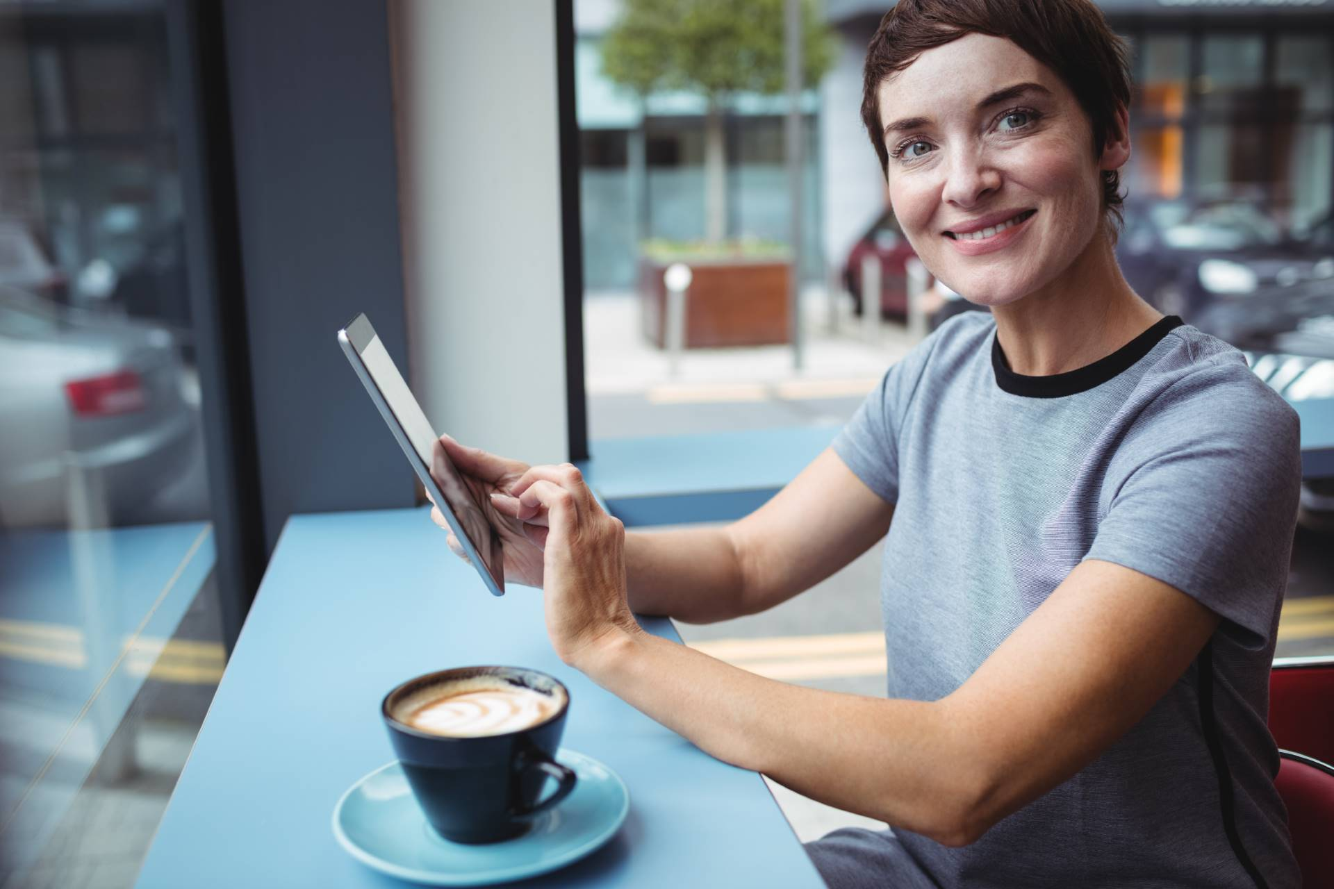 Portrait of businesswoman using digital tablet while having coffee in office